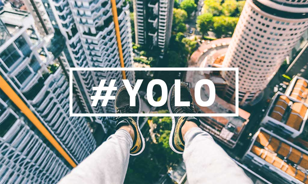 Feet hanging out over city below with text overlay of #YOLO