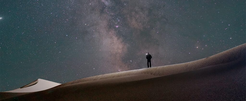 Man alone in field with galaxy
