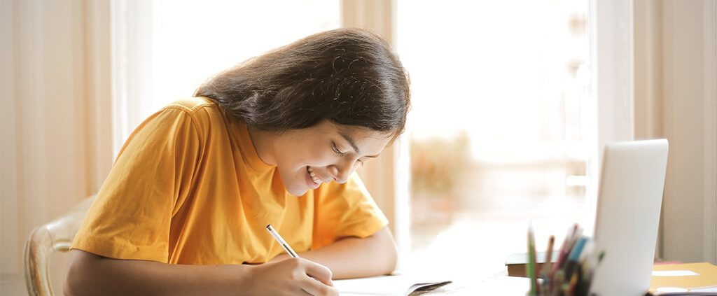 Image of girl writing in her notebook