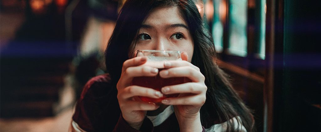 Photo portrait of girl up close holding a coffee cup in front of her face