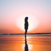 image of lady standing on the beach with sunset behind her