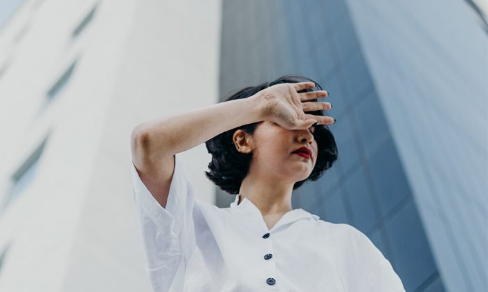 Girl with hand across her face covering