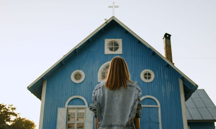 image of lady looking at a front entrance of a church