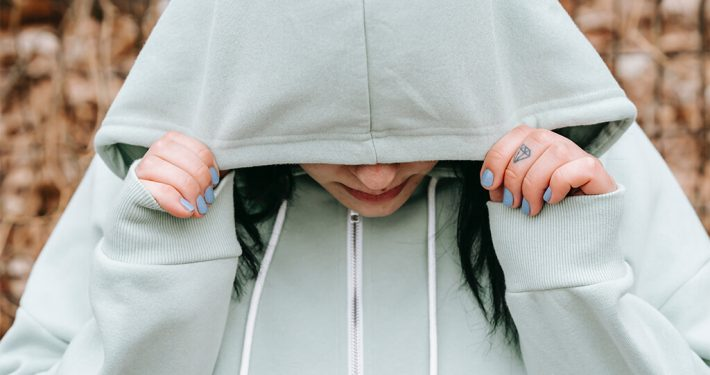 A sad woman covered her face with her hoody jacket