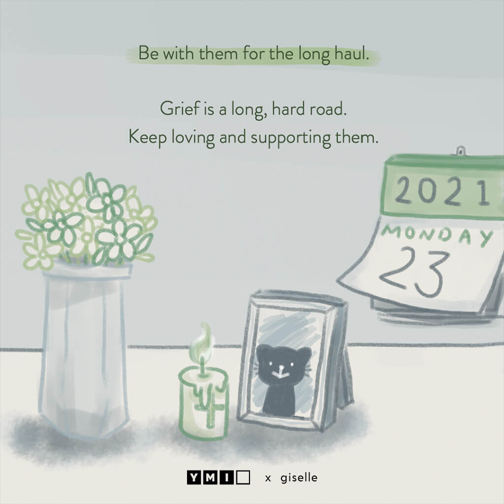 Image of a table top with a vase , calendar and photo frame of a cat