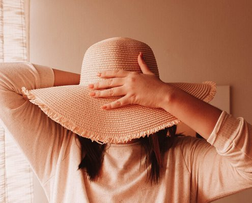 Image of a lady with her face covered by a sun hat