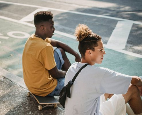 image of 2 men sitting by the road chatting